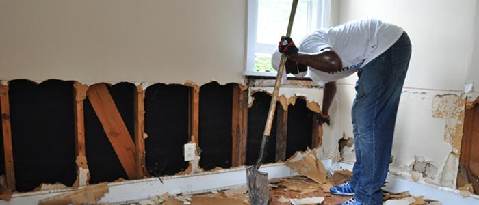 Image of Man Working on House Walls after Flooding